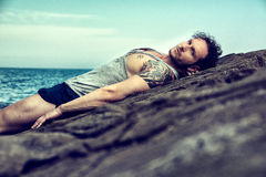 Handsome muscular man on the beach sitting on rocks Stock Images