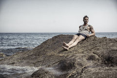 Handsome muscular man on the beach sitting on rocks Royalty Free Stock Image