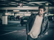 Confident man posing on parking. Handsome muscular man in casual clothing on background of parking Stock Photography