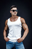 Handsome muscular man in dark glasses and a white shirt. Stock Photography