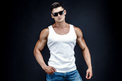Handsome muscular man in dark glasses and a white shirt. Royalty Free Stock Photography