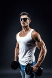Handsome muscular man in dark glasses and a white shirt. Royalty Free Stock Image