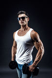 Handsome muscular man in dark glasses and a white shirt. Stock Images