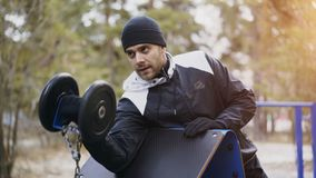 Handsome muscular man doing biceps exercise with barbell at outdoor gym in winter park. Attractive muscular man doing biceps exercise with barbell at outdoor gym Stock Image