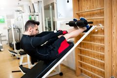 Handsome muscular man doing sit-ups on a incline bench Royalty Free Stock Photos