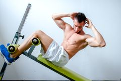 Handsome muscular man doing sit-ups on a incline bench Stock Photography
