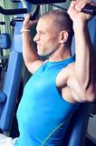 Handsome muscular man exercising in a gym Stock Photo