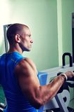 Handsome muscular man exercising in a gym Stock Photos