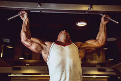Handsome muscular man in gym making elevations. Stock Image