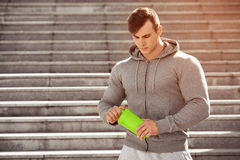 Handsome muscular man holding shaker, outdoors. Young active male drinking water Royalty Free Stock Images