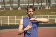 Handsome muscular man holds water bottle. Refreshing. handsome man or guy with muscular body holds plastic refreshing water bottle sunny outdoor in blue royalty free stock photography