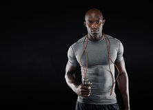 Handsome muscular man with jumping rope. On black background. Fit african model with lots of copy space Stock Photos