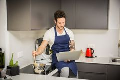 Man in kitchen, cooking and reading on laptop PC Stock Image