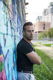 Handsome muscular man leaning against colorful graffiti wall Royalty Free Stock Photo