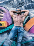 Handsome muscular man leaning against colorful graffiti wall Stock Image