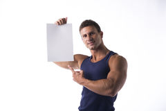 Handsome muscular man pointing to a blank sign Royalty Free Stock Image