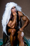 Handsome muscular man in a pose of a thinker. The athlete with long white hair Stock Image