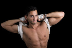 Handsome muscular man pulling up t-shirt on naked torso Royalty Free Stock Image