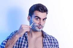 Handsome muscular man shaving with metal razor Royalty Free Stock Image