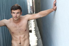 Handsome muscular man shirtless in front of alley way urban wall looking away Royalty Free Stock Photography