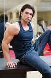 Handsome, muscular man sitting on desk, with jeans and tanktop Stock Images