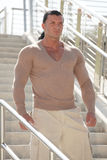 Handsome muscular man on a staircase Stock Images