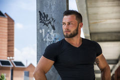 Handsome muscular man standing outdoor in city Stock Photography