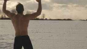 Muscular naked guy shows his force at the winter field background. Handsome muscular man stands at the winter field without t-shirt. Naked man tempers his body stock footage