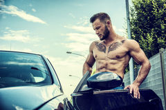 Handsome muscular man with tattooes getting in car Royalty Free Stock Photo