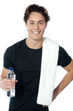 Handsome muscular man with towel. Holding a bottle of water Stock Photos