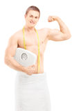 Handsome muscular man in towel holding a weight scale Stock Photo
