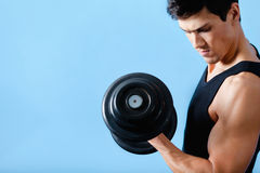 Handsome muscular man uses his dumbbell Royalty Free Stock Photo