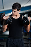 Handsome muscular man uses his dumbbells Stock Photos