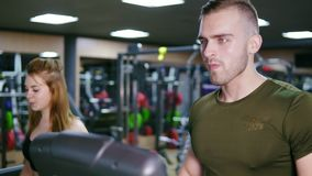 Handsome muscular man is walking on the treadmill in the sport gym warming up before training. Young attractive woman is. Walking behind. Slowmotion shot stock video footage