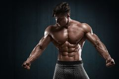 Handsome muscular man on wall background, shaped abdominal. Strong male naked torso abs.  Stock Photo