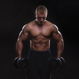 Handsome muscular man working out with dumbbells Stock Photo