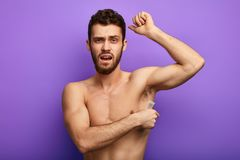 Handsome muscular naked man waxing his armpit stock images