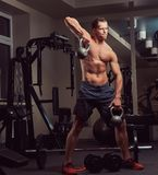 Handsome muscular shirtless bodybuilder male doing exercises with a dumbbell in the gym. stock image