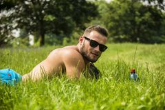 Handsome Muscular Shirtless Hunk Man Outdoor in City Park. Laying on the Grass. Showing Healthy Muscle Body While Looking away Royalty Free Stock Photos