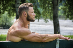 Handsome Muscular Shirtless Hunk Man Outdoor in City Park. Showing Healthy Muscle Body While Looking away, Sitting on Bench Royalty Free Stock Image