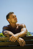 Handsome Muscular Shirtless Hunk Man Outdoor. At Seaside Looking at Camera, Sitting on Bench under the Sun Stock Images
