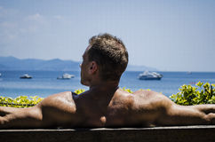 Handsome Muscular Shirtless Hunk Man Outdoor. Muscular Shirtless Hunk Man Outdoor at Seaside Looking at the Sea, Seen from the Back, Sitting on Bench under the Stock Photo