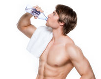 Handsome muscular sportsman drinks water. Stock Image