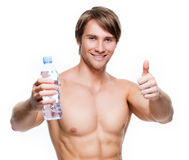 Handsome muscular sportsman holds water. Royalty Free Stock Photo