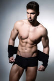 Handsome muscular young bodybuilder showing his muscles and abs Stock Image