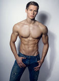 Handsome muscular young bodybuilder showing his muscles and abs royalty free stock photography