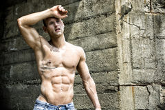 Handsome, muscular young construction worker shirtless. Outdoor, wiping off sweat from forehead Royalty Free Stock Photo