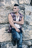 Handsome, muscular young man against rocks Royalty Free Stock Photography