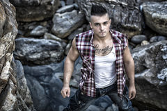 Handsome, muscular young man against rocks Stock Photos