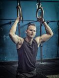 Handsome young man exercising with rings Royalty Free Stock Photo